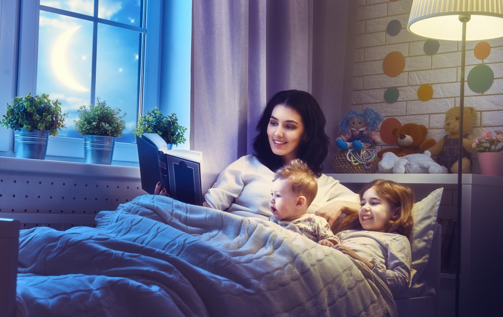 mother reading to their children image